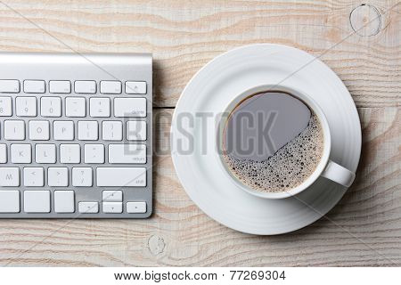 Computer keyboard and cup of hot coffee on a white rustic table. High angle shot in horizontal format.