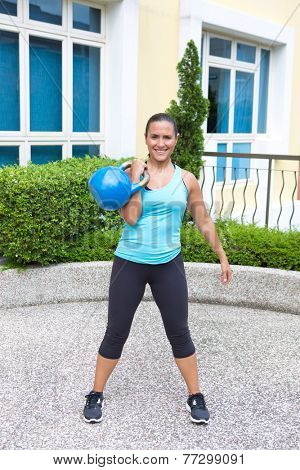 Beautiful sporty hispanic woman in blue training with kettlebell in the clean pose