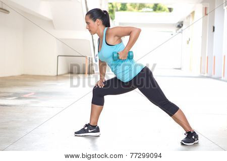 Beautiful sporty hispanic woman in blue  demonstrating the rowing routine with blue dumbbell outdoors
