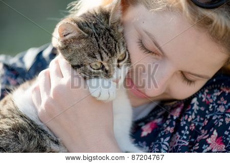 Blonde woman playing with her adorable cat
