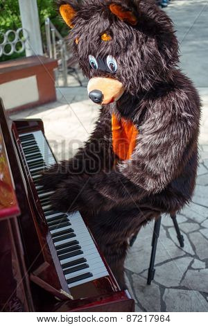 actor dressed as bear plays music on piano on the bandstand in the park