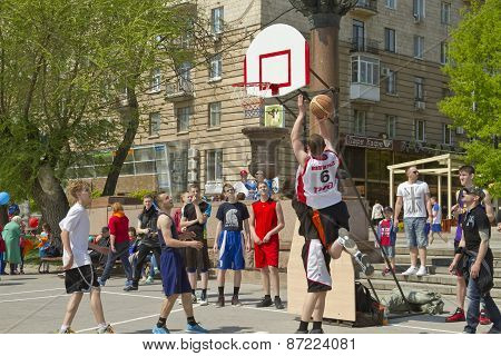 Teenagers play streetball on the open-air asphalt ground