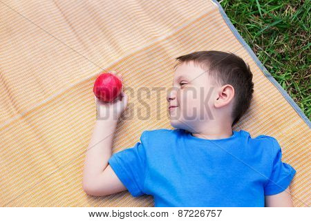 Boy Laying On Mat And Look At Apple