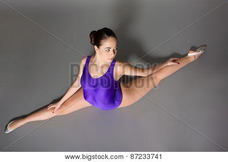 Young Female Contortionist In Purple Leotard On Dark Background