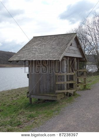 Wooden shelter lakeside view landscape photographed at Wimbleball Lake Country Park near Dulverton in Somerset poster