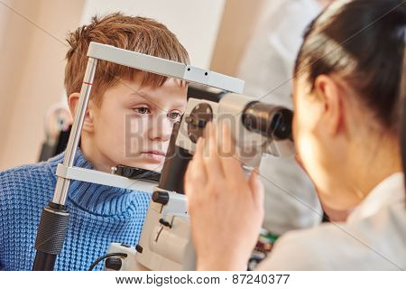 Child optometry. female optometrist optician doctor examines eyesight of little boy patient in eye ophthalmological clinic