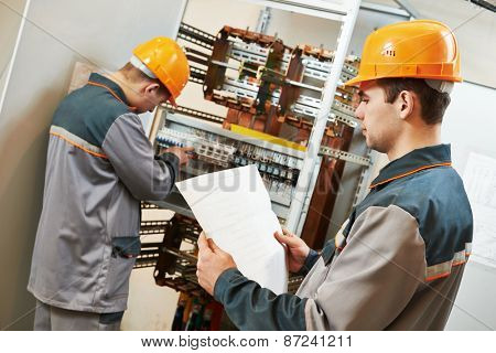 two electrician builder engineer works with electric cable wiring of fuse switch box poster