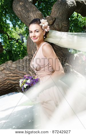 beautiful happy bride in beige dress smiling standing among green trees