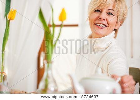 Woman grabbing coffee or tea pot
