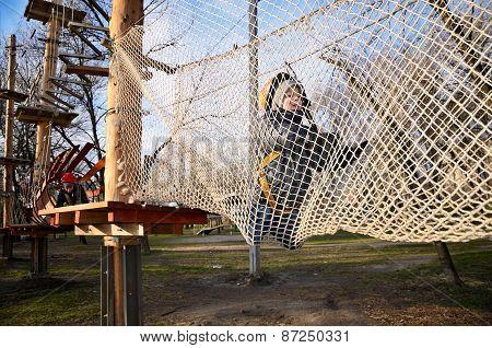 Little Boy Crawling On Suspension Net Bridge. Horizontal