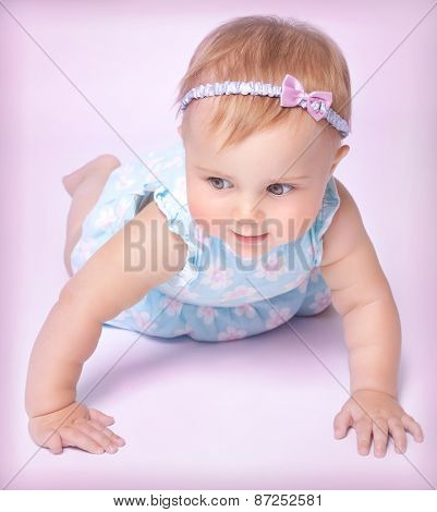 Cute little baby girl crawling in the studio on pink background, wearing nice dress and stylish head accessories, happy joyful childhood