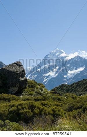 Mount Cook ahead, beyond the lush green valley and rock outcrops