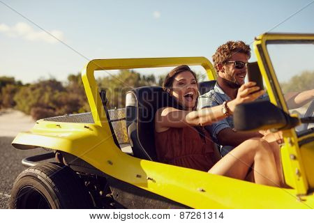 Excited happy couple enjoying road trip in their car. Man driving the car young woman taking a selfie from her mobile phone. poster