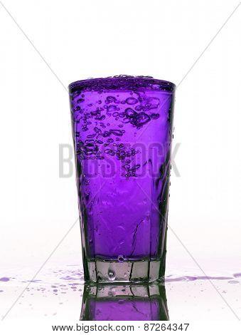 Glass of splashing Purple lemonade isolated on white background