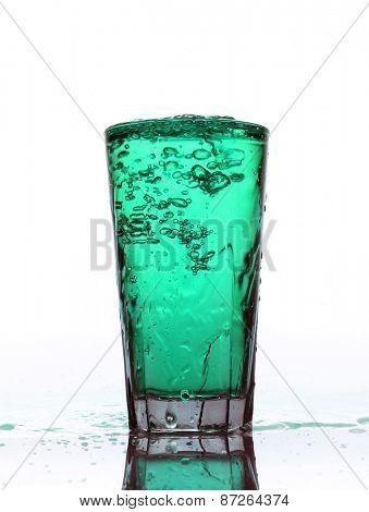 Glass of splashing Turquoise lemonade isolated on white background