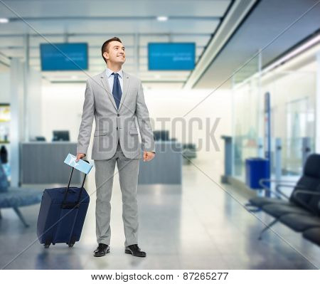 business trip, traveling, luggage and people concept - happy businessman in suit with travel bag and air ticket over airport background