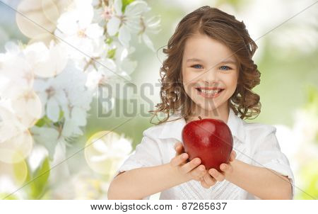 people, children, healthy eating and food concept- happy girl holding red apple over summer or spring garden background