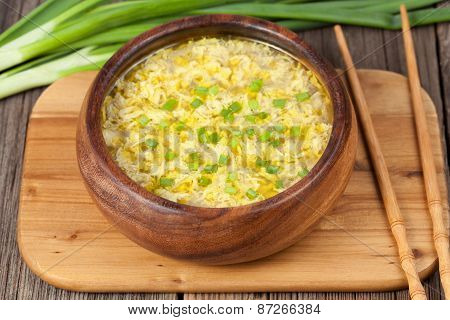 Yellow egg drop soup with chiken broth chinese healthy lunch in wooden bowl on vintage background poster