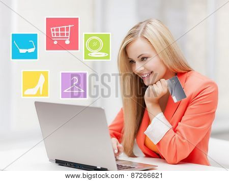 online shopping, sale and people concept - happy businesswoman with laptop and credit card at office