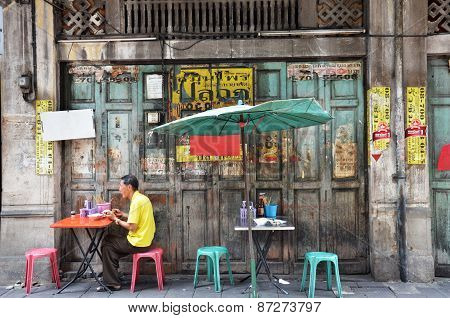Unidentified Man Eats On A Street In Chinatown District, Bangkok, Thailand