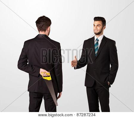 Two opposing businessman shake hands, one of them hiding a weapon behind his back poster