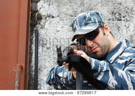 Military Caucasian Man In Urban Warfare Aiming With Grifle