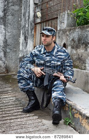 Caucasian Military Man In Urban Warfare Sitting And Holding Automatic Weapon