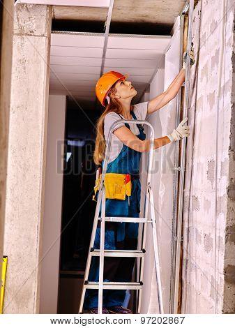 Happy woman in builder uniform indoor. poster