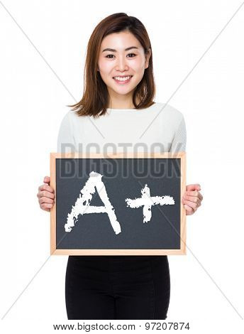 Young woman with the blank of blackboard showing mark A plus