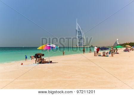 DUBAI, UAE - 2 APRIL 2014: People on the Jumeirah Beach in Dubai, UAE. Jumeirah Beach is a white sand beach that is located and named after the Jumeirah district of Dubai.