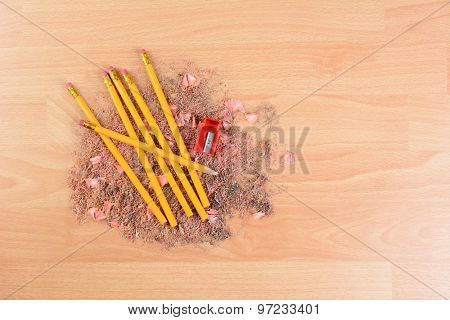 High angle view of yellow number 2 pencils on a school desk with a sharpener and shavings. Horizontal with copy space. Back to school concept.