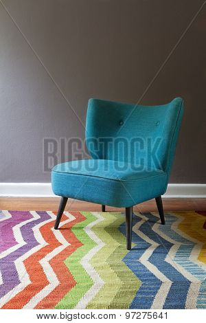 Single Teal Blue Armchair And Colorful Chevron Pattern Rug Interior