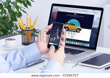 Uber App On The Iphone Display In Man Hands And Uber Website On The Macbook Pro Screen