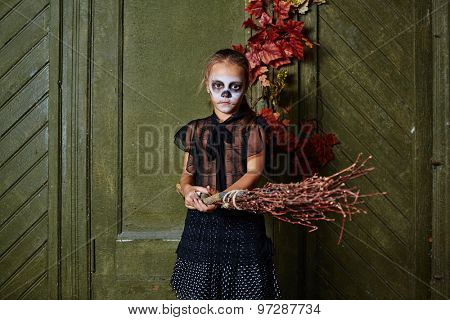 Little witch with painted face holding broom and looking at camera in decrepit house