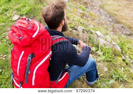 adventure, travel, tourism, hike and people concept - man hiker with red backpack sitting on ground poster