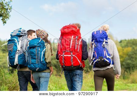 adventure, travel, tourism, hike and people concept - group of friends walking with backpacks from back poster