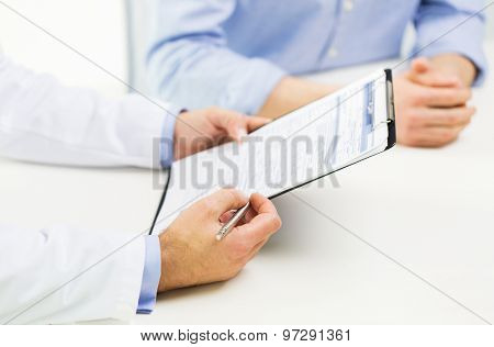 medicine, health care, people and prostate cancer concept - close up of f male doctor and patient hands with clipboard