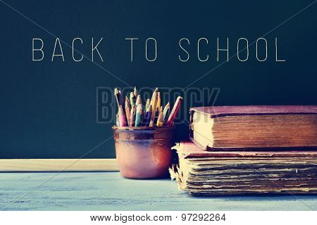 some pencils in a pot, some old books on a blue school desk, and the text back to school written on a chalkboard, with a filter effect