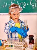 Child in glove holding flask in chemistry class. poster