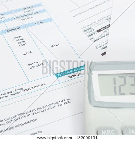 Unpaid Utility Bill And Calculator Over It - Close Up Studio Shot