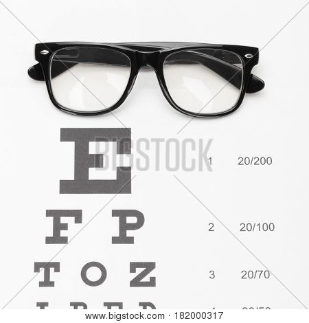 Close Up Shot Of A Table For Eyesight Test With Glasses Over It