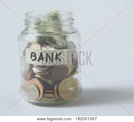 Money jar with coins on wood table.