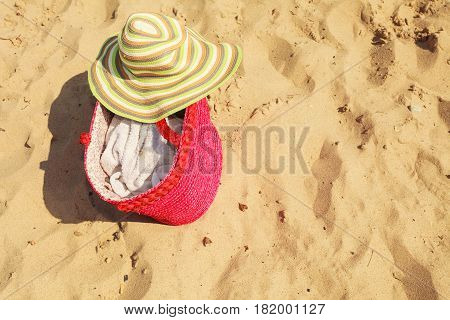 Seasonal specifics. Yellow summer female hat and big red shopper bag lying on sand on beach.