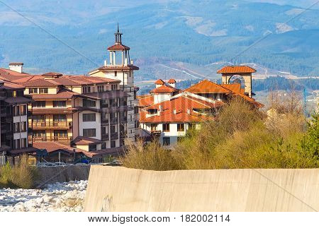 Bansko, Bulgaria spring view with trees, mountains landscape and house tower