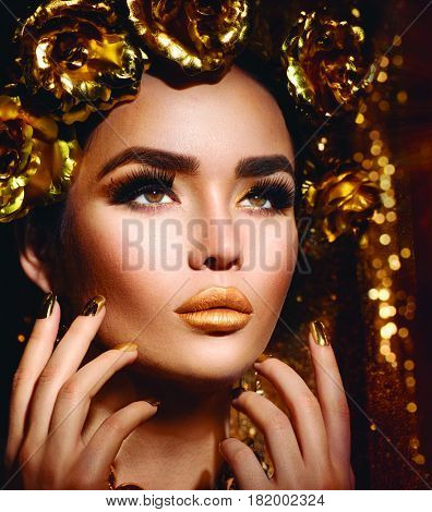 Gold Woman holiday makeup. Beauty fashion model girl with Golden make up, hair and jewellery on glowing background. Gold wreath and necklace. Fashion art portrait, Hairstyle, manicure and make up