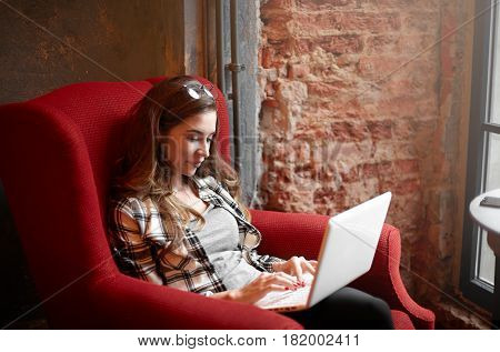 Caucasian student female with cute smile wearing in check shirt keyboarding something on laptop sitting in big red armchair in cafe chatting with friend using free wi-fi. Copy space wall for text