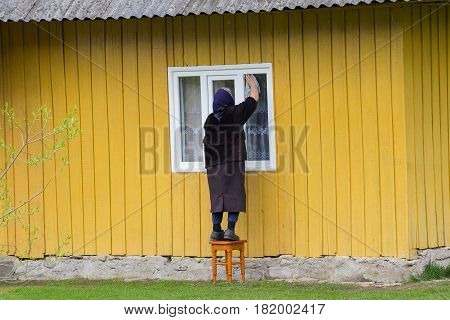 Elderly woman washes the window of a rural house. People