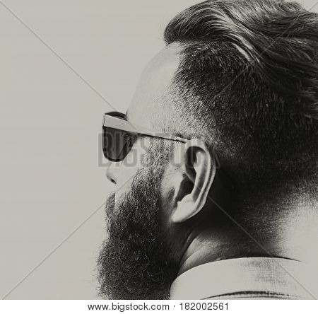 Portrait of a bearded man in sunglasses with a stylish haircut. Black and white.
