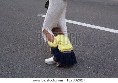 Little girl hides behind her mother's legs. People