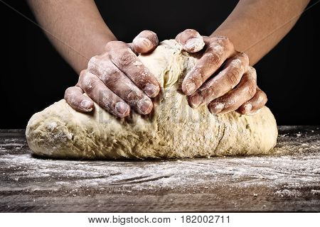 Woman's hands kneading the dough on dark background.